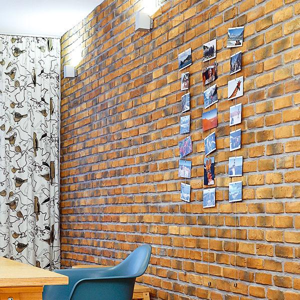Vlastnoručne vyrobená dekorácia na tehlovej stene. Fotografie zciest na oceľových lankách sťažidlami na koncoch. Krásne jednoduchá ahravá inšpirácia od majiteľky.