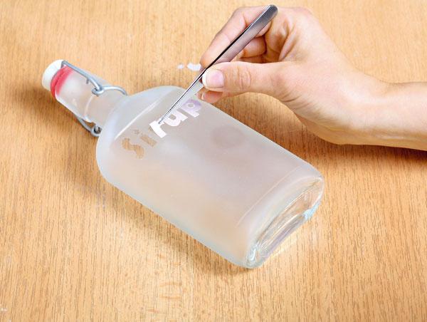Keď je postrek suchý, písmenká odlepte pinzetou. Na fľašu môžete aj vyškrabávať rôzne obrazce. Sprej sa vodou nezmyje, môžete ho však zoškriabať.