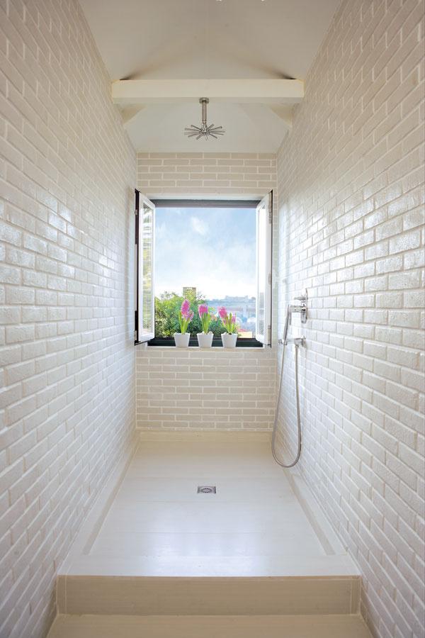 Veľkorysý sprchovací kút nie je od zvyšku kúpeľne oddelený zástenou ani závesom – majiteľka bytu totiž nemá rada malé auzavreté priestory.