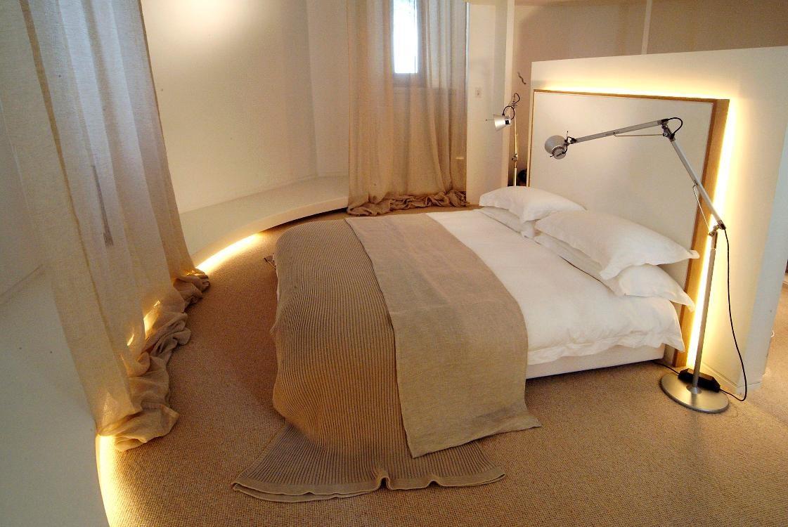 V spálni majiteľa domu nájdeme prírodne tkaniny, od tkaného koberčeka až po ľanové závesy a posteľnú bielizeň. Čelo postele je zozadu osvetlené
