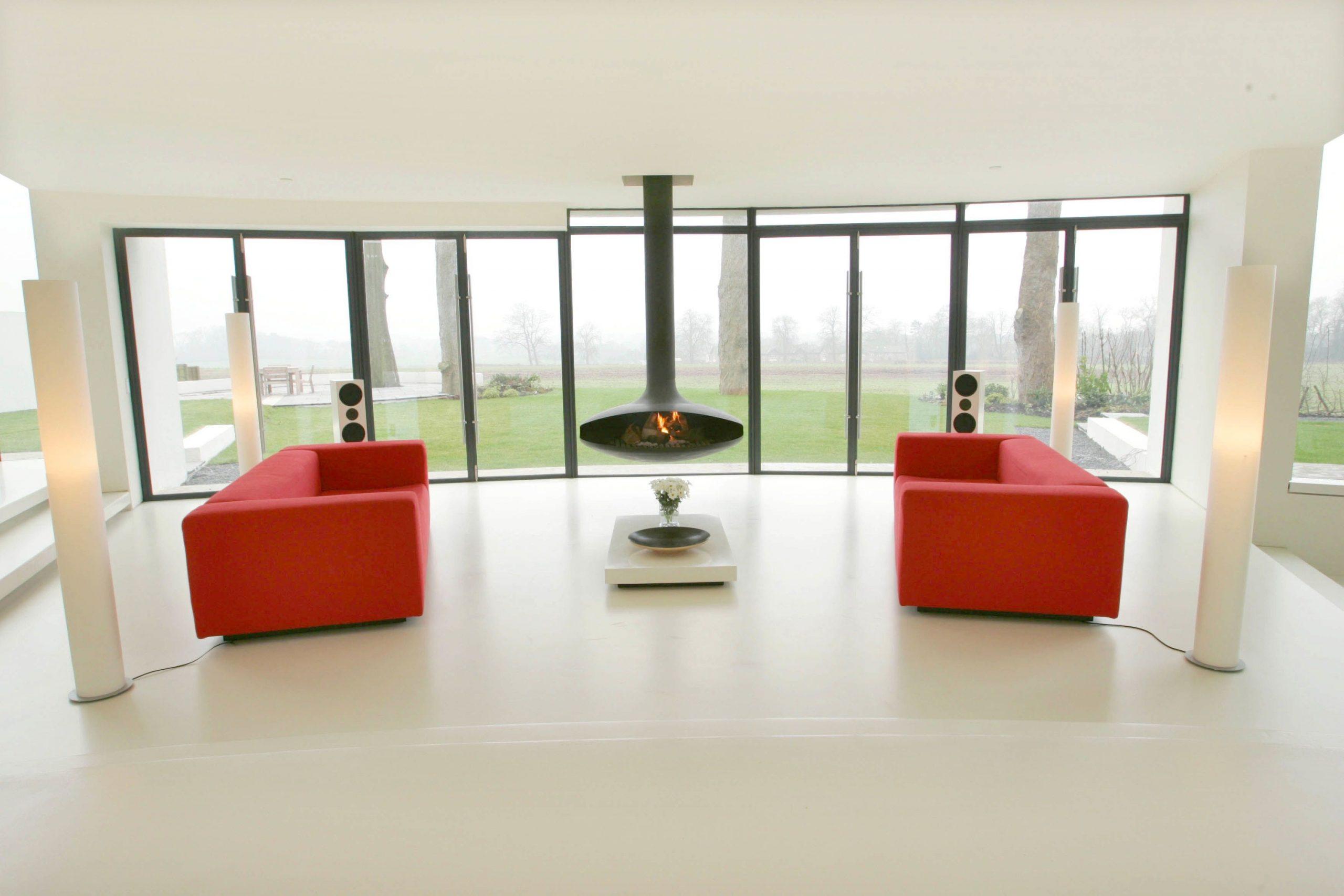 Dve žiarivo červené pohovky sú symetricky umiestnené medzi štyrmi identickými lampami a uprostred vystupuje zo stropu atypický kozub.