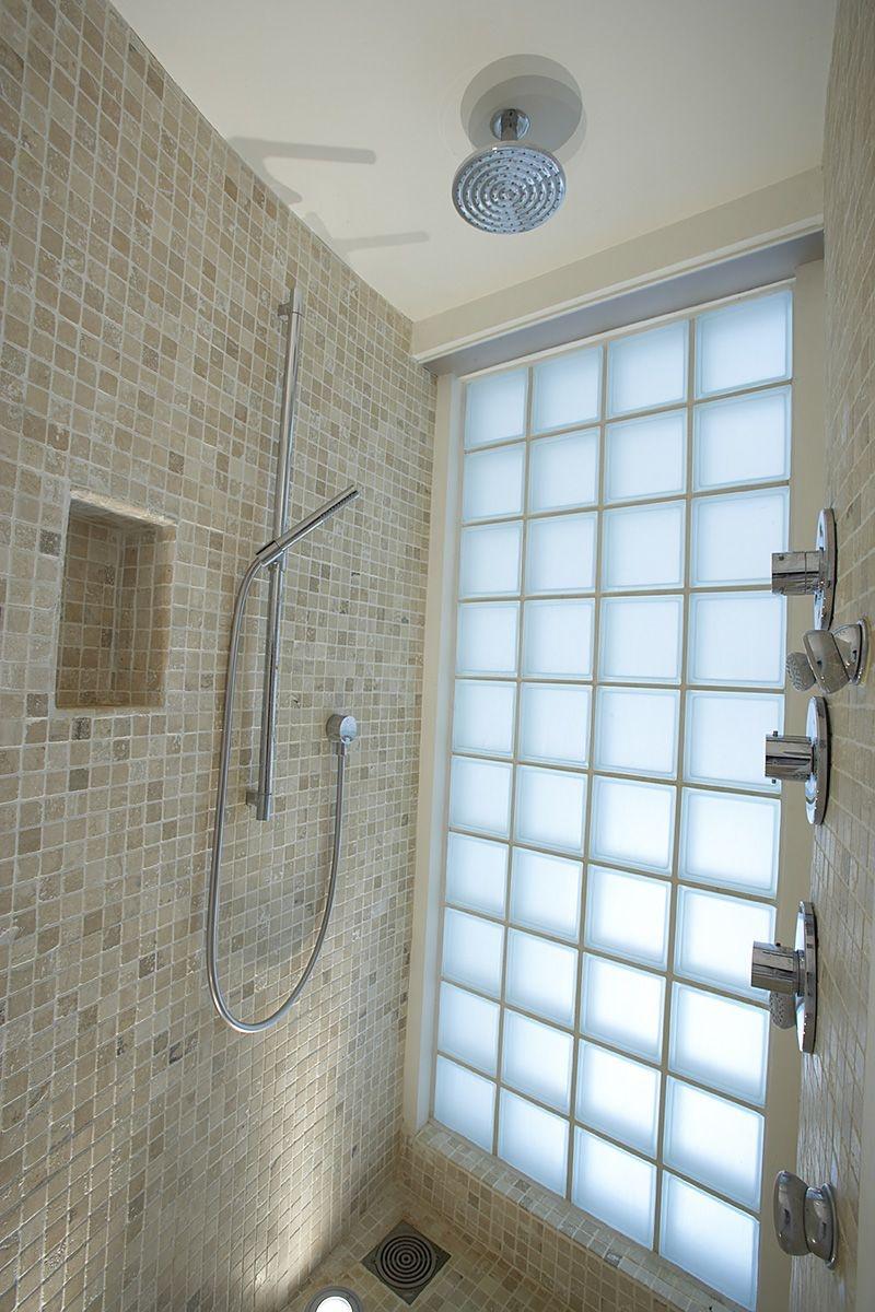 Sprchový kút s presklenou stenou ponúka počas dňa prirodzené svetlo.