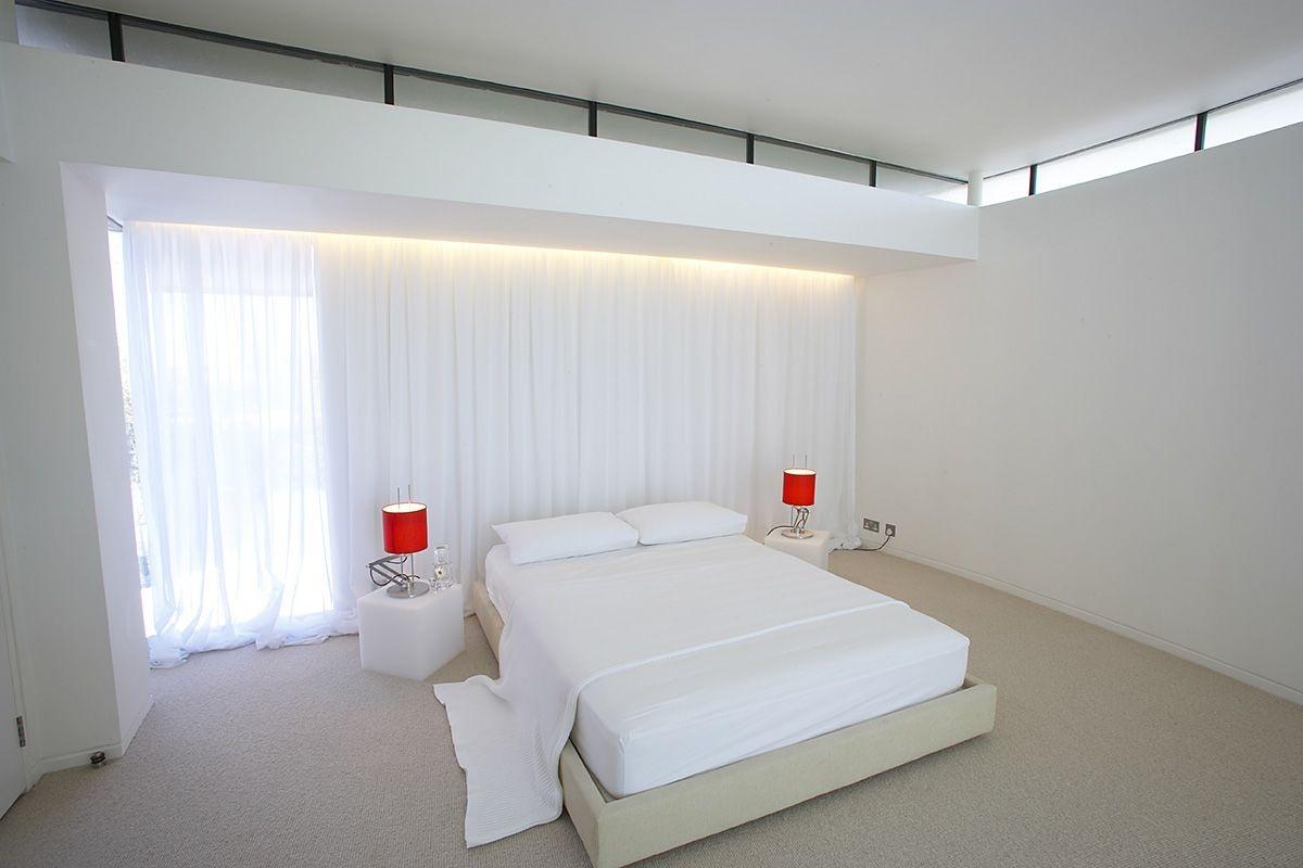 Červené stolové lampy oživujú biely interiér hosťovskej spálne.