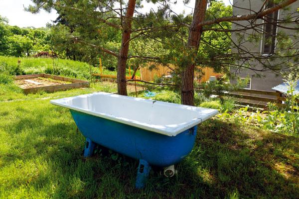 Vaňa sa do kúpeľne nevošla, takže sa premenila na vonkajší bazén alebo relaxačnú zónu v letnom období. Stará liatinová vaňa dostala nový modrý náter a v tieni borovíc ponúka dokonalý relax.