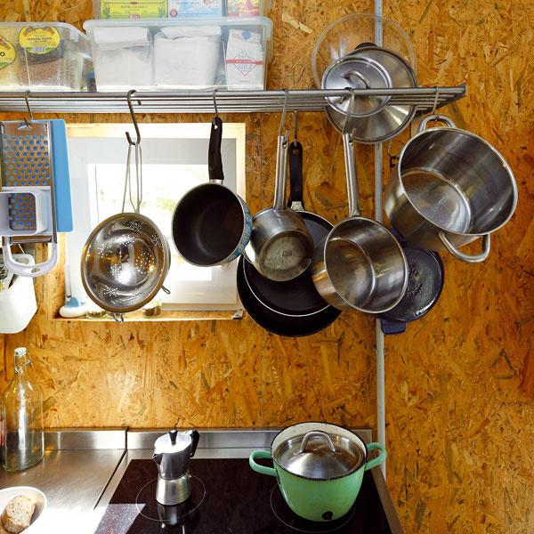 Vkuchyni je všetko poruke. Namiesto konvenčných horných skriniek použili kovovú policu, ktorá dostala viacero funkcií.