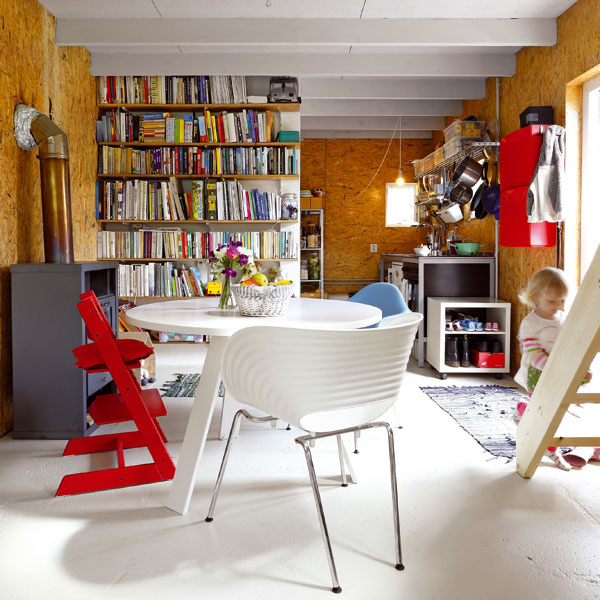 Celému obytnému priestoru na prízemí dominuje jedálenský stôl s pestrými dizajnovými stoličkami.