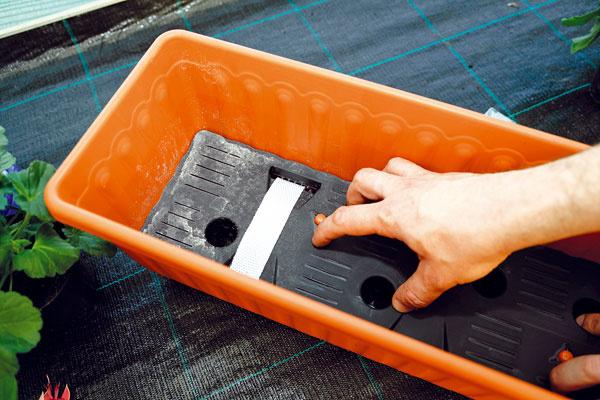 SKLADANIE HRANTÍKA. Samozavlažovacia nádoba funguje tak, že substrát vnej prijíma vlahu pomocou širokých knôtov zo zásobovacej časti svodou. Prvým krokom bude poskladanie nádoby ainštalácia knôtov – ich konce musia smerovať do spodnej časti, kde bude voda.