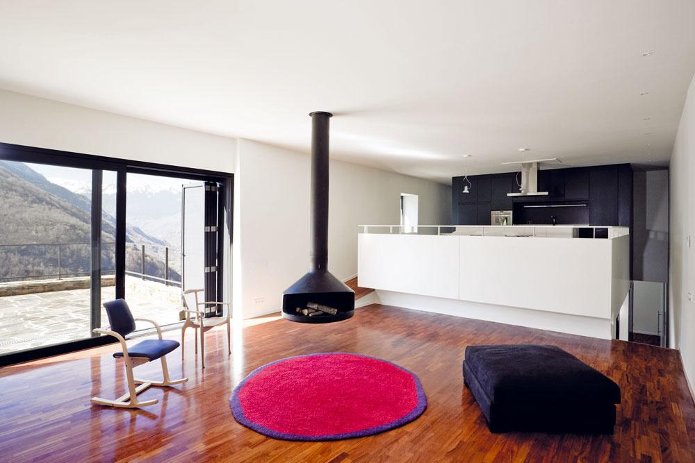 Obytná časť apartmánu na druhom nadzemnom podlaží je prepojená sveľkou terasou. Kozub zavesený vpriestore naznačuje tradičné usporiadanie domu, keď sa rodina stretávala okolo ohniska.