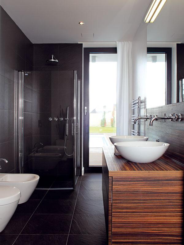 Pôsobivá kombinácia obkladu adlažby vo farbe bridlice, elegantnej bielej keramiky adreva wenge je zámerne rovnaká voboch kúpeľniach v dome.