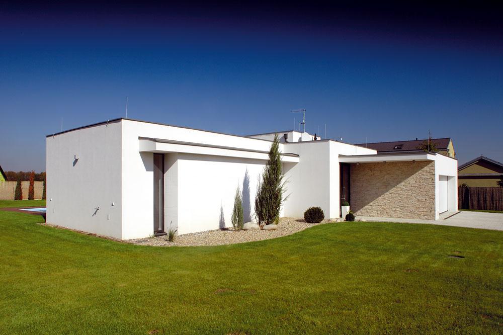 Smerom k ulici vystupuje zjednoducho tvarovaného domu dvojgaráž, ktorá zároveň pomáha vytvoriť chránený priestor pred vstupnými dverami.