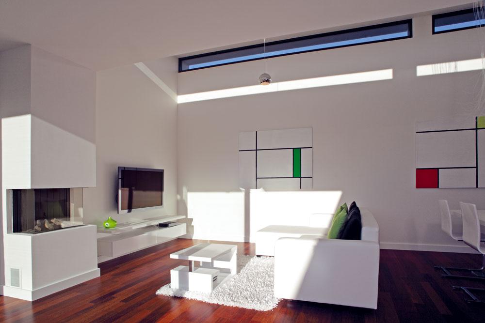 Oživením čistej architektúry domu je svetlo – cez úzke okná vo zvýšenej časti otvoreného priestoru vytvára na stenách premenlivé svetelné efekty a vyníma denný priestor zhraníc štandardu.