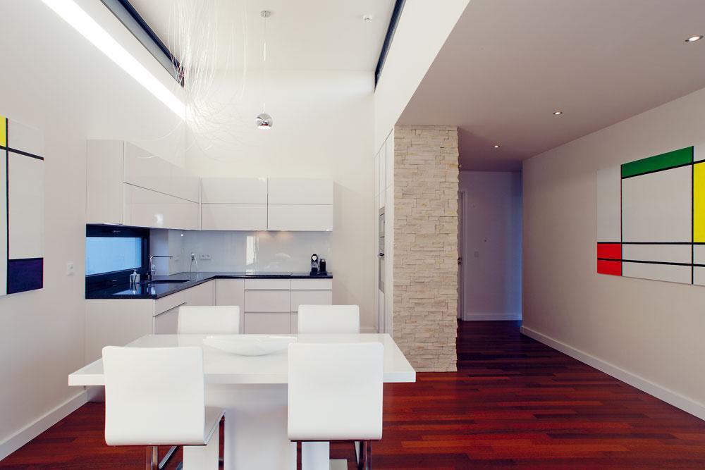 Minimalistický interiér otvoreného denného priestoru dokonale ladí sobrazmi na stenách. Sbielymi stenami anábytkom kontrastuje podlaha zdreva merbau, ktorá celý dom pocitovo prehriala.