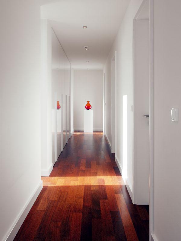 Čistý interiér nadväzuje na minimalistickú architektúru. Dominantná biela je podľa architekta farba, ktorá nikdy neomrzí a dá sa efektne oživiť, podľa majiteľov práve ona vnáša do domu pocit slnka.