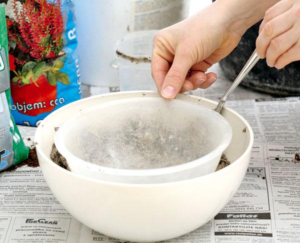 Na korkové zátky položte druhú, menšiu misku a pomocou lyžice vyplňte priestor betónovou zmesou. Zmes naplňte asi 1 cm pod okraj vnútornej misky, aby ste ju potom mohli ľahšie vybrať. Do vnútornej misky vložte kameň alebo kúsok tehly ako ťažidlo.
