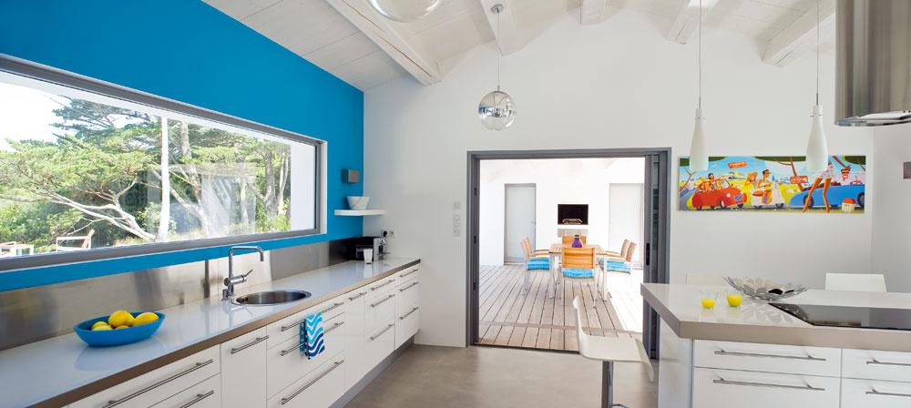 Kuchyňa je priestranná, jednoduchá aúčelná, sbetónovou podlahou amoderným vybavením. Uchváti tyrkysovou stenou sobrovským oknom, zktorého je pri práci nádherný výhľad na kanál.