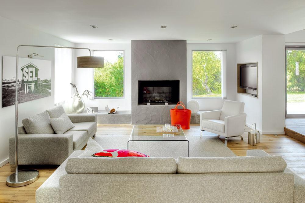 Sjedálňou bezprostredne susedí priestranná obývačka. Jej dominantou je kozub sdvoma veľkými oknami po oboch stranách.