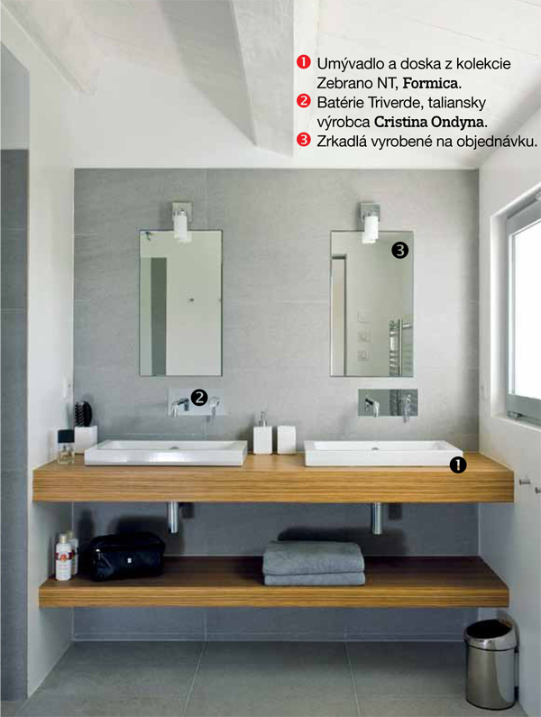 Sjednoduchým sivým obkladom ladia biele geometrické umývadlá, príjemný kontrast vytvára drevená umývadlová doska.