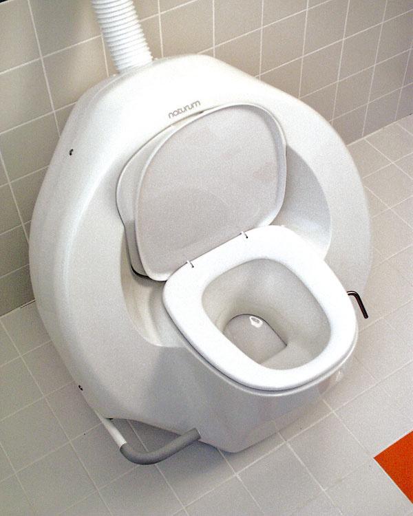 """Rotačná separačná kompostovacia toaleta oddeľuje tuhý odpad od tekutého, ztuhého pripravuje kompost. Vyzerá takmer ako klasická, za misou je však izolovaný bubon kompostéra s10-litrovým zásobníkom srašelinou (4-členná rodina ho naplní asi za mesiac). Vďaka rašeline je príprava kompostu rýchlejšia apremiešanie zabraňuje zápachu aj bez chemikálií. Kompostér pracuje na mechanickom princípe otáčania bubna – po použití párkrát stlačíte pedál aje """"spláchnuté""""."""
