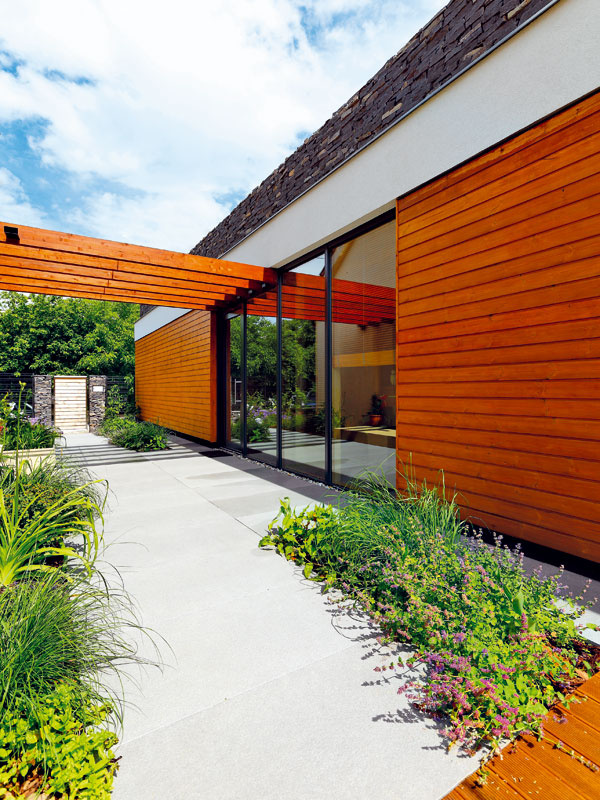 V exteriéri zvolil architekt pôsobivú kombináciu dreva a sivej farebnosti, reprezentovanej miestnym kameňom, hliníkovými okennými rámami a elegantnou gresovou dlažbou.