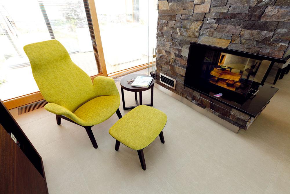 Rozľahlý interiér člení okrem nábytku aj kozub, ktorý vymedzuje miestečko na relaxačný kútik. Väčšina nábytku (vrátane kresielka s podnožkou a kruhového stolíka) tu je od značky Poliform.