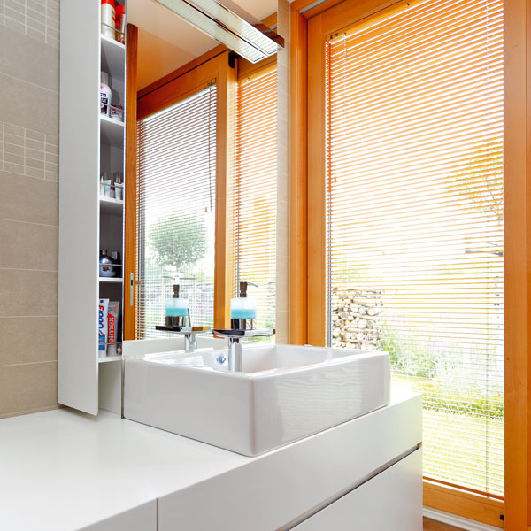 Nábytok v kúpeľni je tiež vyrobený na mieru. Domáca pani si aj tu pochvaľuje dostatok úložných priestorov, niektoré, napríklad zásuvka za zrkadlom, sú naozaj nápadité.