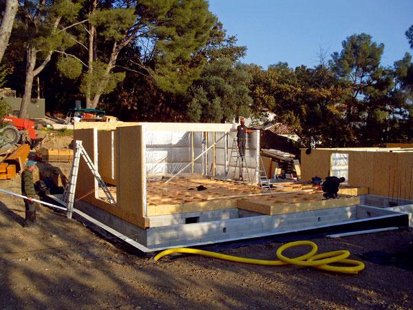 Prvý deň výstavby panelovej drevostavby atypickej vily. Zo základovej dosky sa dvíhajú prvé panely.