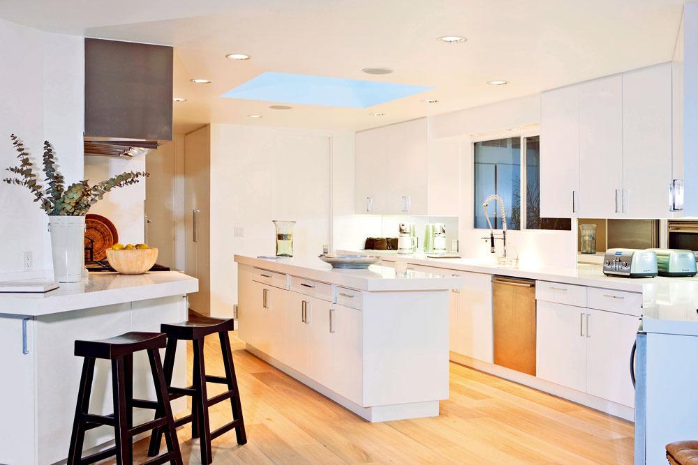 Kuchyňa zariadená jednoduchým bielym nábytkom, otvorený, pokojne plynúci priestor bez priečok a veľkorysé zasklené steny, cez ktoré sa otvára výhľad na mesto, spoluvytvárajú nenápadnú noblesu domu.