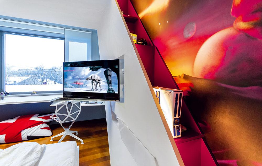 Televízor ahernú konzolu skryl autor interiéru do krídlovitej sadrokartónovej steny vedľa postele, praktické využitie majú aj poličky za ňou.