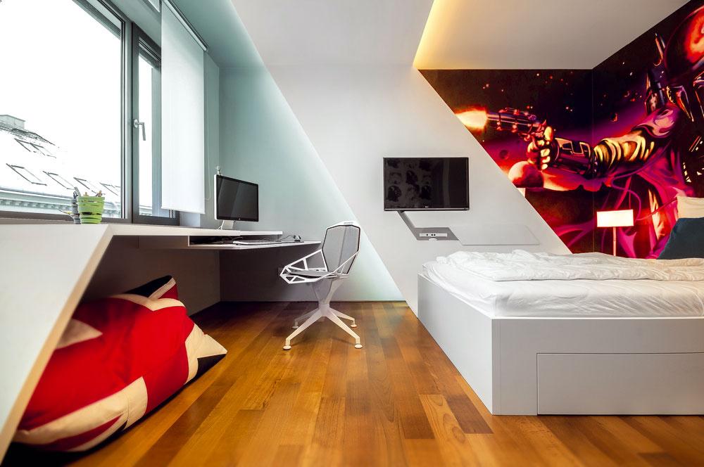 Rovnaké tvaroslovie ako sadrokartónová stena si ctí aj ďalší výrazný interiérový prvok, pracovný stôl pod oknom oproti posteli.