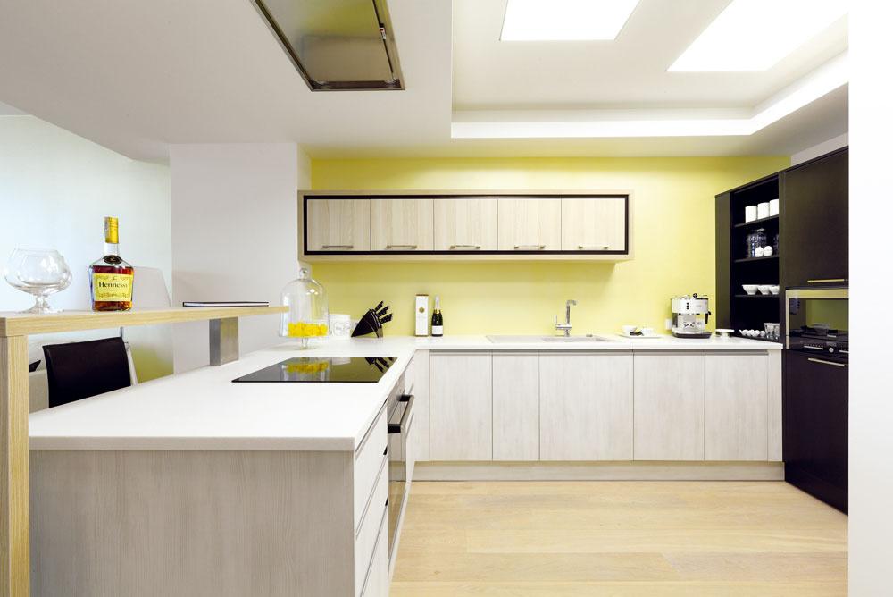 Znúdze cnosť: pod znížený strop snízkou podchodnou výškou, kde je ukrytá klimatizácia, umiestnila architektka kuchynskú linku.