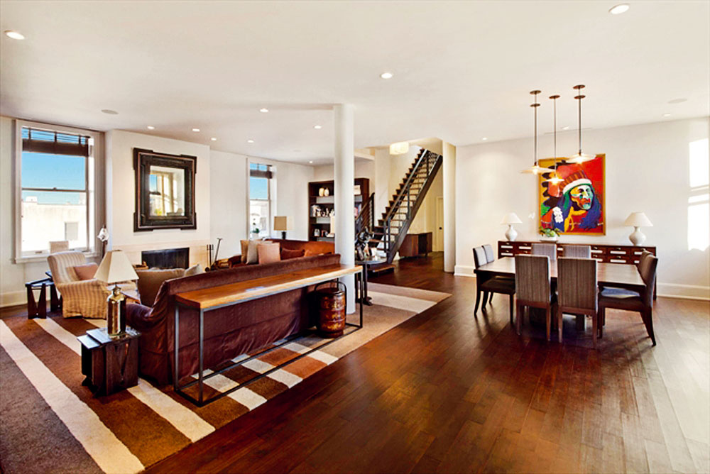 Obývačka na spodnom podlaží sa nesie v útulnom koloniálnom duchu. Rovnako ako o poschodie vyššie, ani tu nechýba kozub či priamy kontakt s kuchyňou, ktorú oddeľujú veľké posuvné dvere.