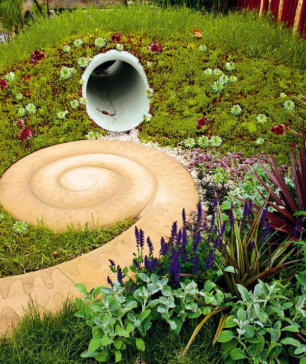 Čím zaujať deti vzáhrade? Čo tak netradičným chodníkom vtvare slimáka. Ajkeď je to betón, netvári sa vtejto kompozícii príliš cudzo. Vhodné riešenie do záhrad sdetským kútikom.