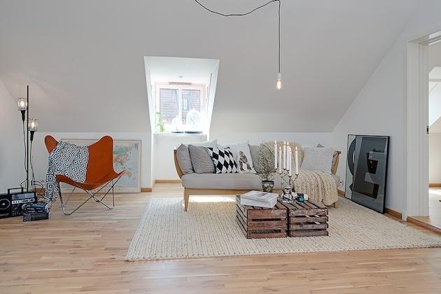 Obývačka s nevšednými prvkami, minimalistickou lampou a stolom z prepraviek.