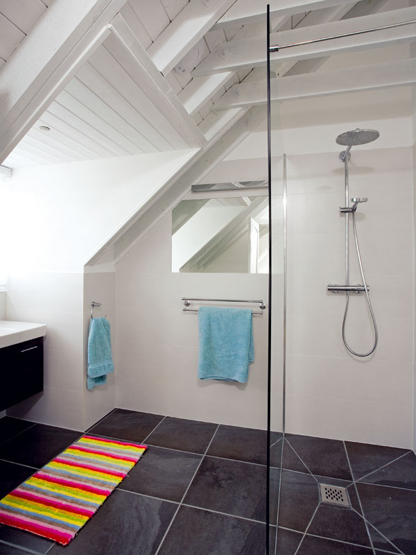 Na poschodí sú tri kúpeľne,všetky vrovnakom duchu, sbielym kabátom na stenách ačiernymi topánkami na podlahe. Minimalistický dizajn necháva vyniknúť výrazným prvkom drevenej konštrukcie šikmej strechy.