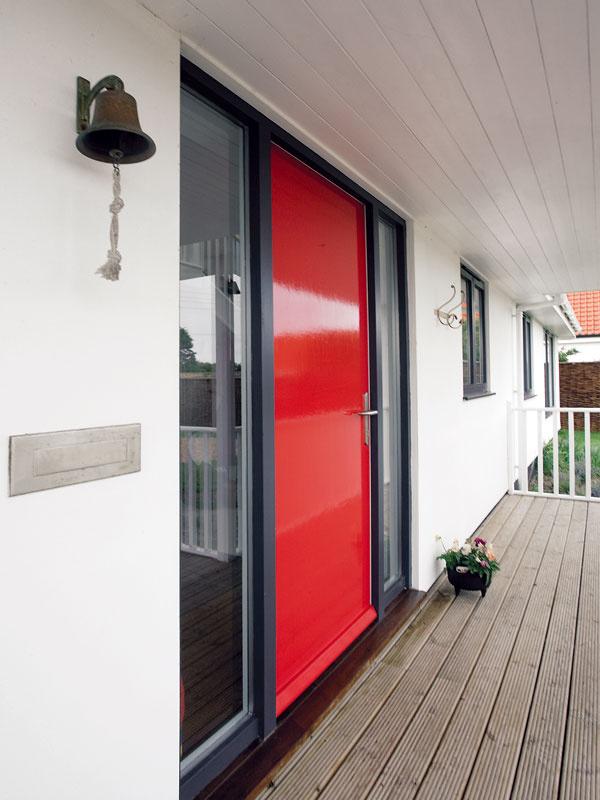 Dvere vžiarivej farbe oživujú jednoduchú bielu prednú fasádu sverandou. Okno vhale pri dverách odhalí krásny priehľad domom až na more.
