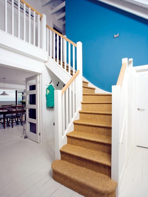 Zhaly sa vychádza na poschodie domu. Tu použili jedinú výraznú farbu na stene, ale aj tá je pod taktovkou mora doplnená opieskovú farbu koberca zmorskej trávy na schodoch.