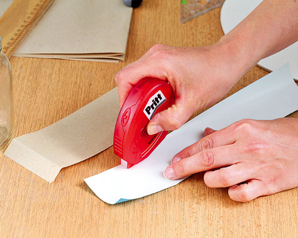 Na druhú stranu farebného papiera naneste lepidlo – drží okamžite. Výhoda tohto lepidla spočíva v tom, že papier sa pri ňom nezvlní ako pri tekutom lepidle. Lepidlo naneste aj na hnedý papier a prilepte ho na pohár.