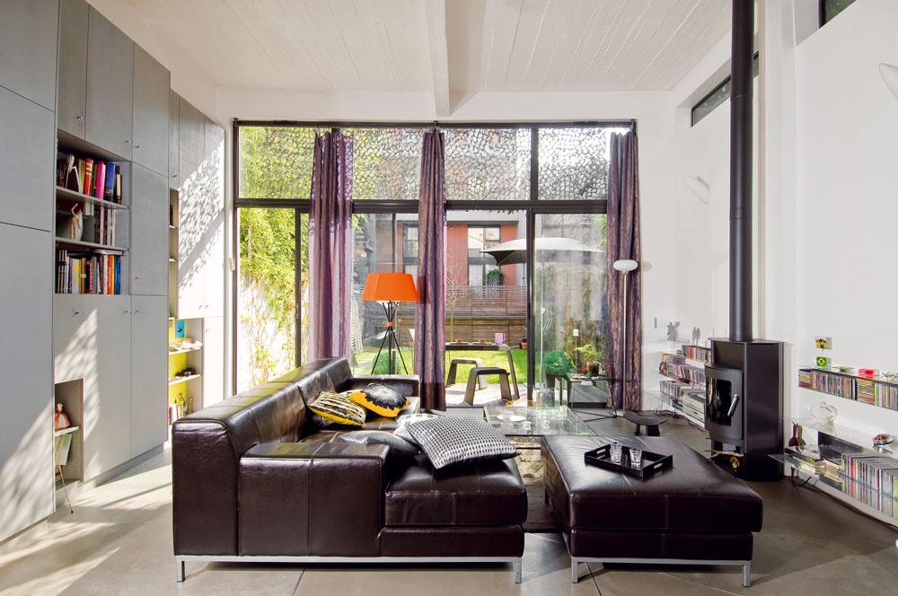 Vďaka vysokým stropom pôsobí obývacia izba naozaj vzdušne. Dominuje jej obrovská kožená sedačka na kovových nožičkách. O väčšie pohodlie sa starajú vankúše s rôznymi motívmi.
