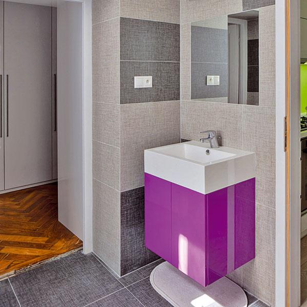 Kúpeľňa sa síce oproti pôvodnej očosi zmenšila, ale ostalo tu dosť miesta na všetko, čo majitelia považovali za potrebné. Farebne neutrálny základ necháva vyniknúť detaily v žiarivej fuksiovej farbe.