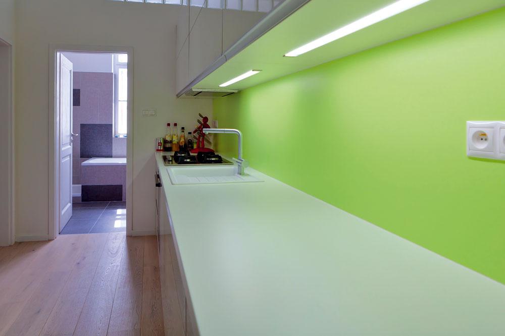 Do kuchyne, ktorá nemá vlastné okno, vpúšťa denné svetlo zo susednej kúpeľne pás sklobetónu tesne pod stropom. Miestnosť opticky zosvetľujú aj lesklé plochy nábytku vo svetlých farbách.