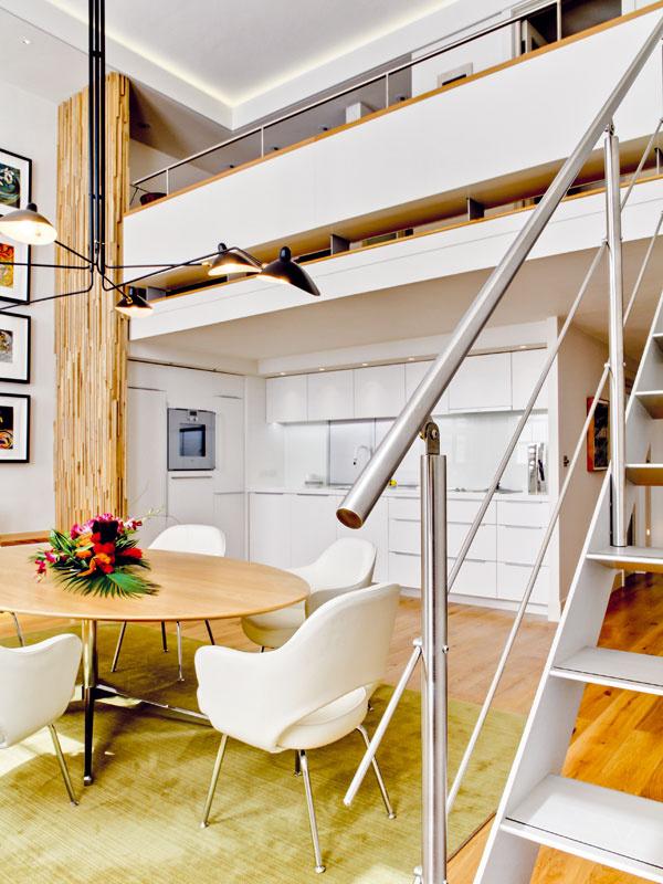 Impozantná výška bytu priam ponúkala možnosť vytvoriť tu poschodie, i keď snižším stropom, ako je bežné. Rozhranie otvorenej advojpodlažnej časti tvorí vzdušná galéria, pod ktorou je priestor decentnej kuchyne.