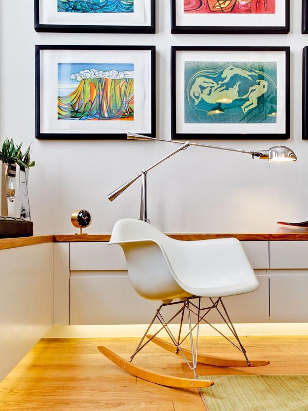 Minimalistický základ interiéru so zariadením vdecentnej farebnosti oživujú pestré obrazy anadčasový retro nábytok.