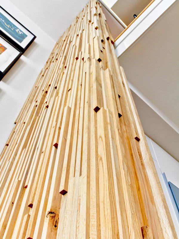 Vertikálna skulptúra zdubového dreva určuje rozhranie vysokého spoločenského priestoru apokojnej dvojpodlažnej časti bytu.