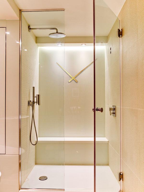 V kúpeľni tikajú hodiny netradične priamo na stene sprchovacieho kúta. Tu zrejme avizovaných päť minút v sprche dodržiavajú.