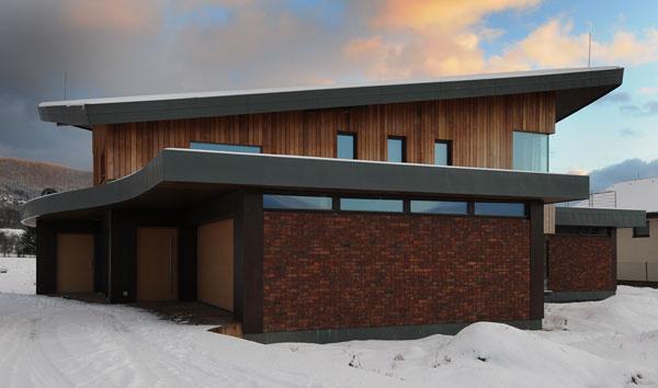 """Spojenie materiálov – tehlový obklad a cédrové drevo pôsobia jednotne a zdôrazňujú ideu domu v """"prírodnom prevedení"""""""