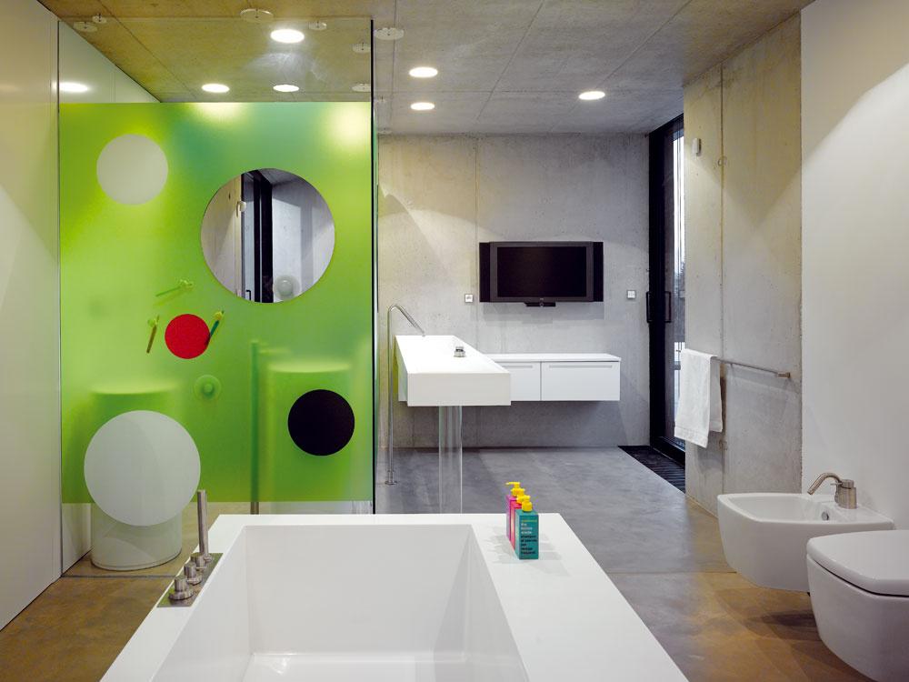 Kúpeľne sú farebne aj tvarovo najodvážnejšími interiérmi vdome. Oživuje ich kontrast zelených plôch sbetónom akruhov so všadeprítomnou lineárnosťou.