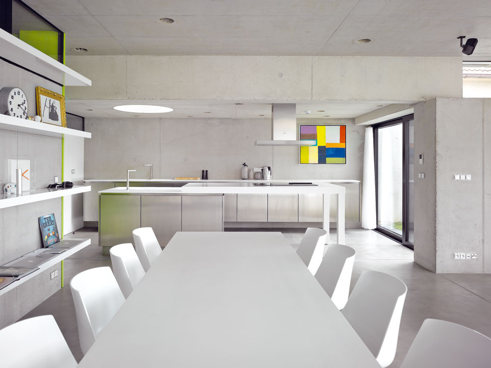 Priestor je zariadený jednoducho afunkčne, sfarbami atvarmi sa narábalo ako skorením. Minimalistickú kombináciu betónu abieleho nábytku účinne oživuje niekoľko farebných detailov.