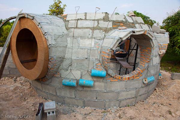 """Na výrobu špecificky vystupujúcich okenných """"rámov"""" zasa Steve použil veľké kruhové konštrukcie z tamojšieho dreva, ktoré obložili tehlami"""