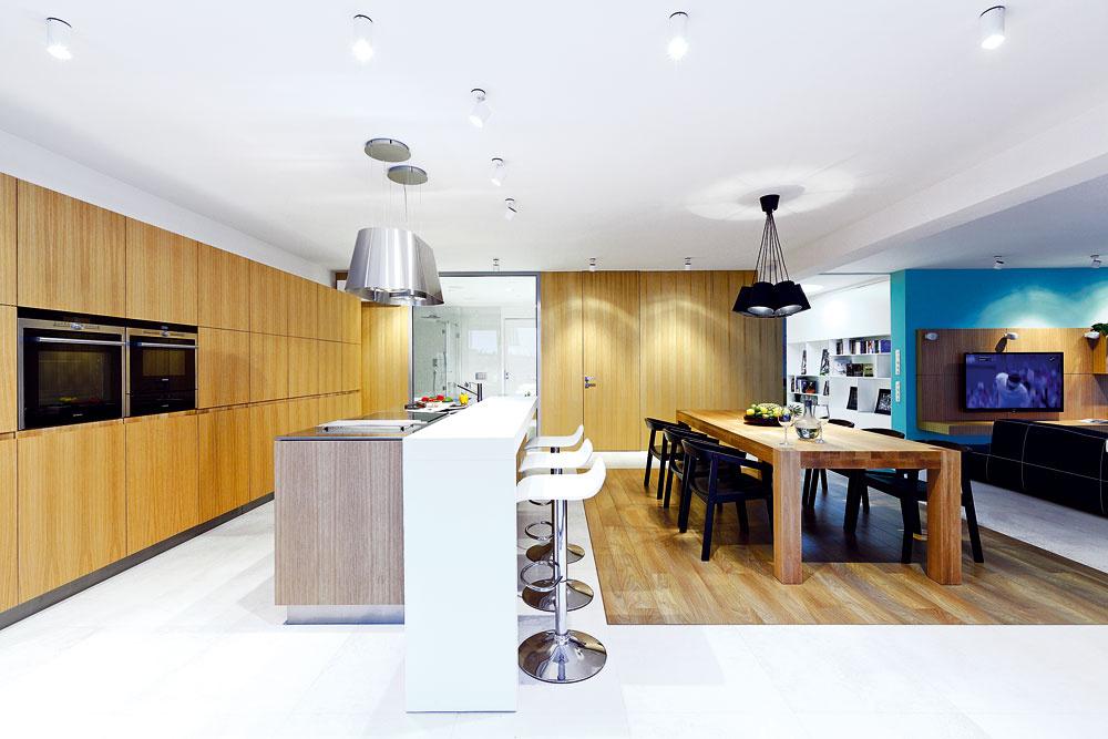 """Podlaha je kombináciou veľkoplošnej gresovej dlažby adrevených parkiet. Jedáleň aj obývačkové sedenie sú umiestnené na teplejších apríjemnejších drevených """"ostrovoch""""."""