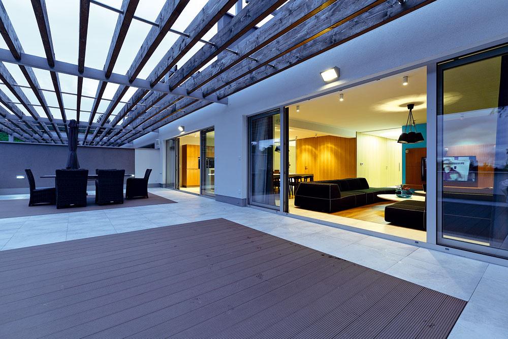 Bez bariér. Po odsunutí dvojkrídlových sklenených dverí sa bariéra medzi interiérom aexteriérom stratí aterasa splynie sdennou časťou bytu do celku srozlohou vyše 150 m2.